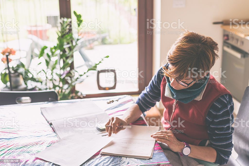 Woman working at home, reading and handwriting documents stock photo