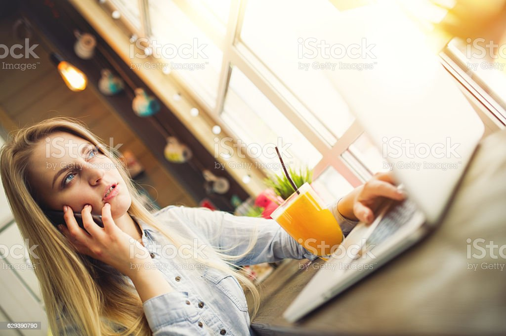 Woman working at laptop and talking about something on phone stock photo