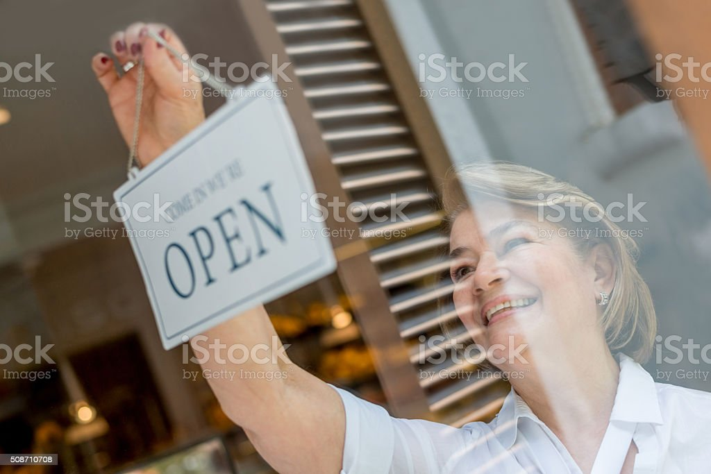 Woman working at the bakery hanging an open sign stock photo