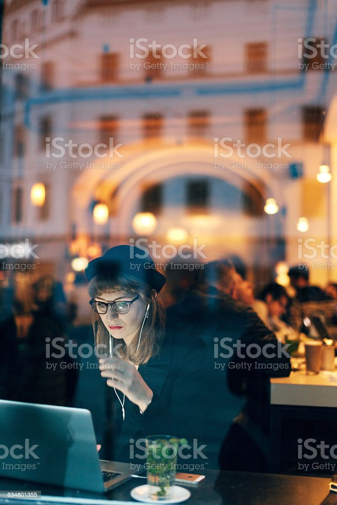 Woman working from Cafe with Free WiFi stock photo