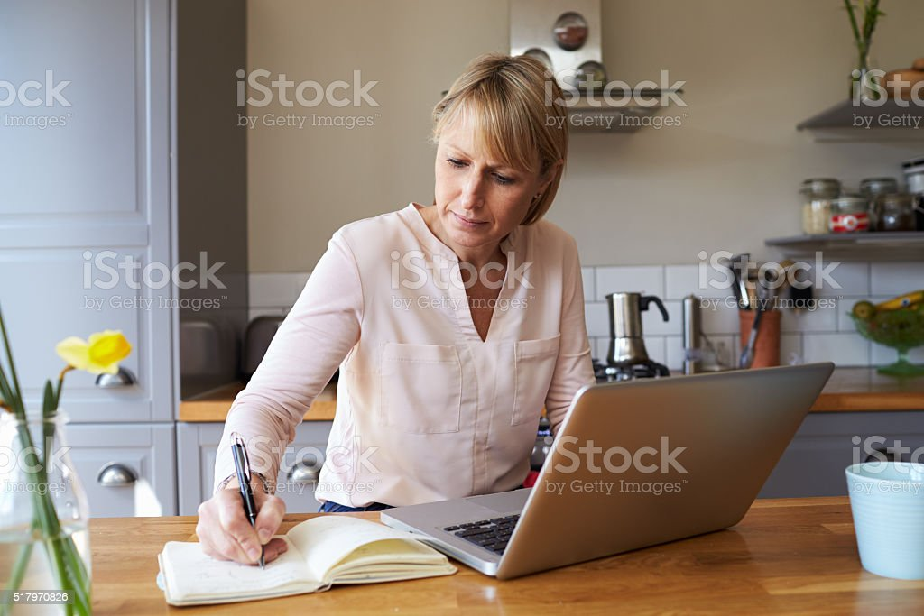 Woman Working From Home On Laptop In Modern Apartment stock photo