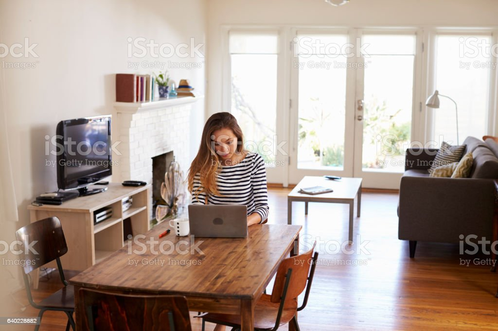Woman Working From Home Using Laptop On Dining Table stock photo