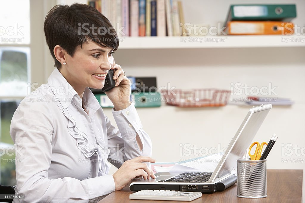Woman Working From Home Using Laptop Talking On Phone stock photo