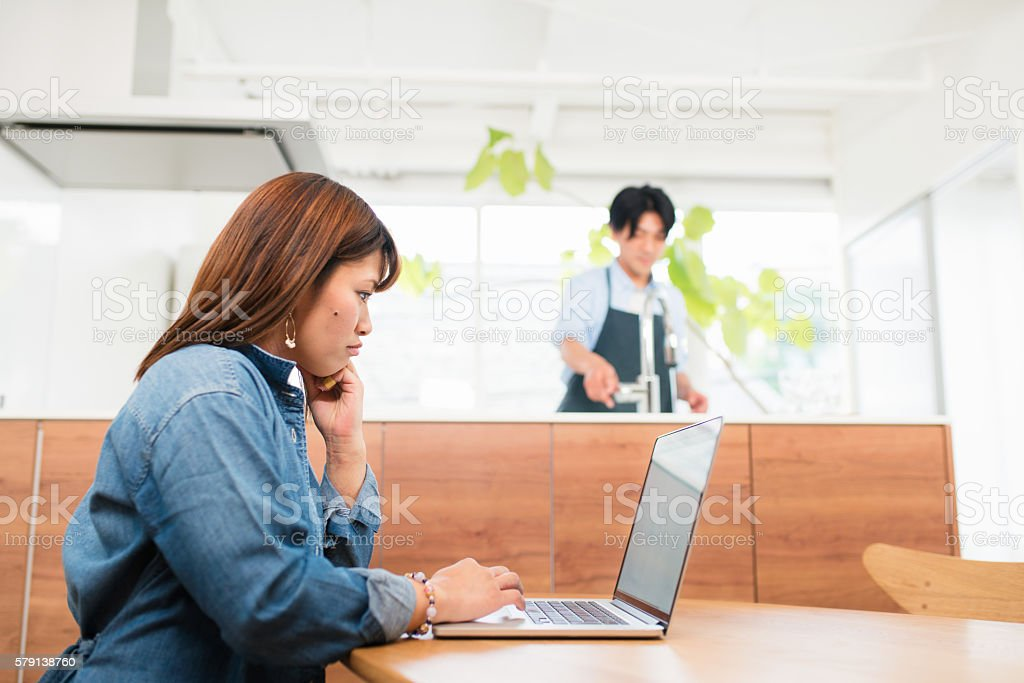Woman working from home whilst husband washes dishes stock photo