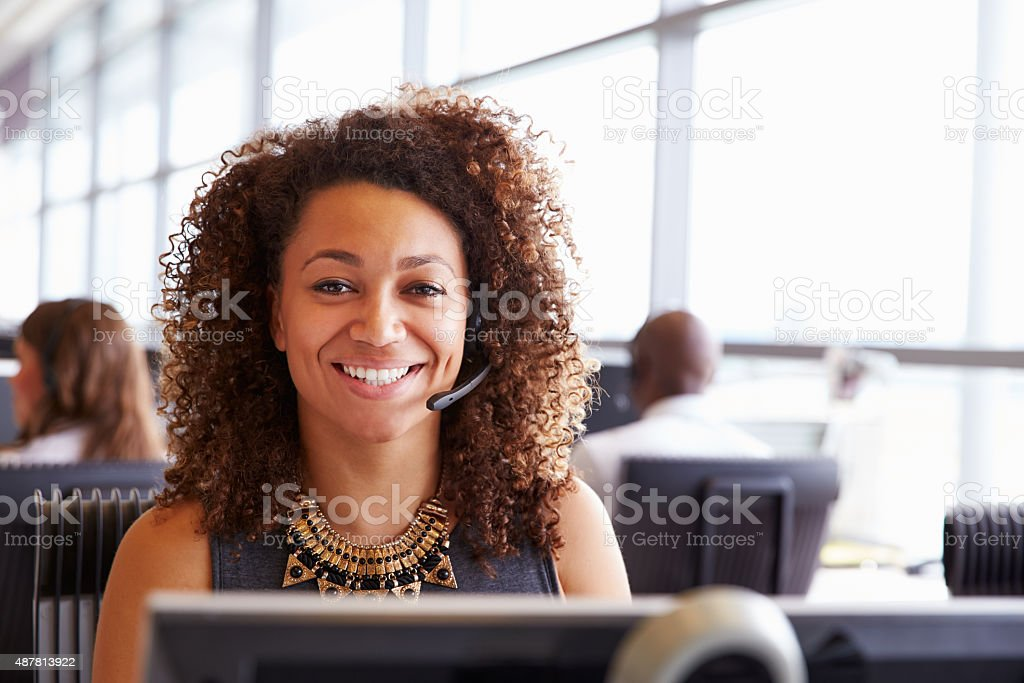 Woman working in a call centre, looking to camera, close-up stock photo
