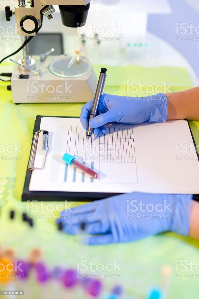 Woman working in a laboratory, using felt pen stock photo