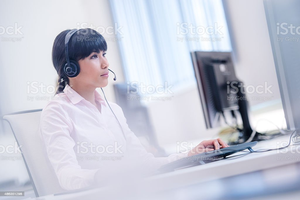 Woman working in call centre office stock photo