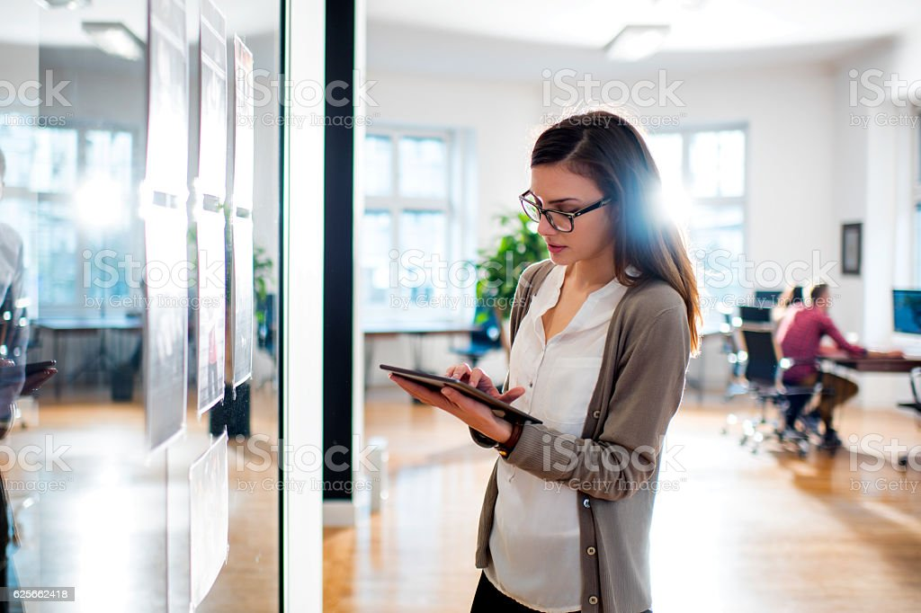 Woman working in front of glass in office stock photo