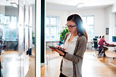 Woman working in front of glass in office