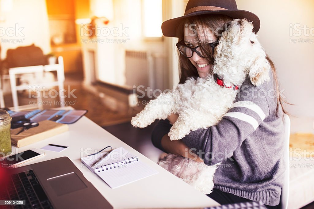Woman working in her office and hugging her puppy stock photo