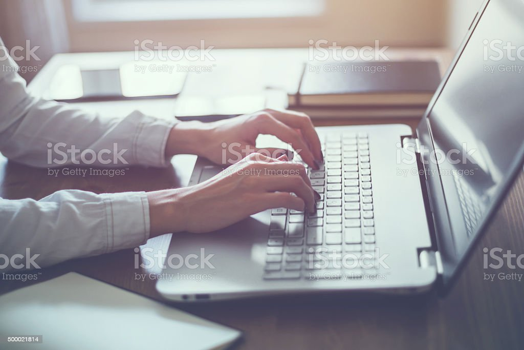 Woman working in home office hand on keyboard close up stock photo