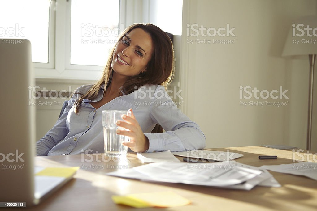 Woman working in home office smiling at camera stock photo
