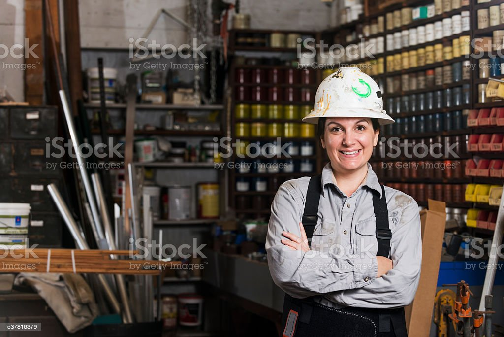 Woman working in printing plant wearing hardhat stock photo