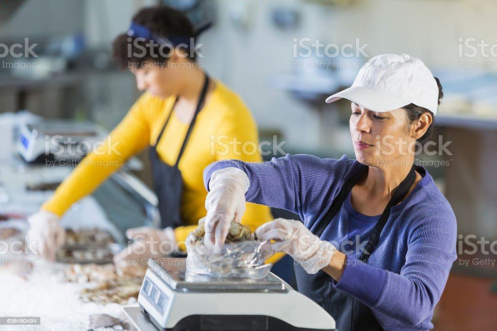 Woman working in seafood market, weighing raw shrimp stock photo