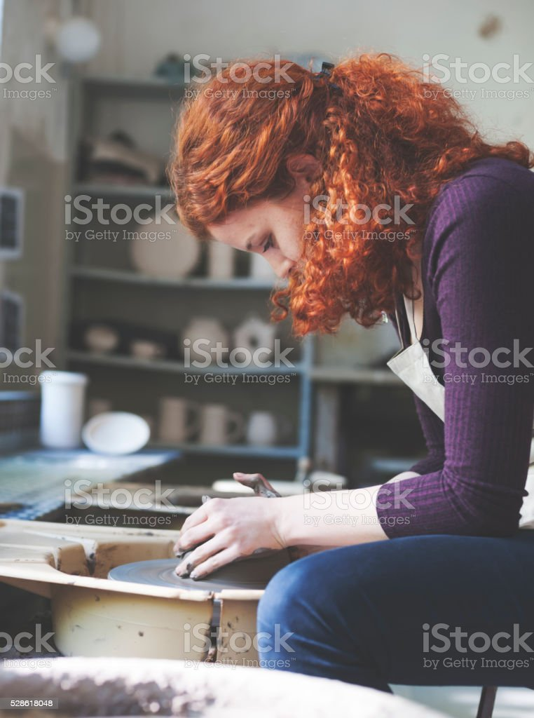 Woman working on a clay vase stock photo