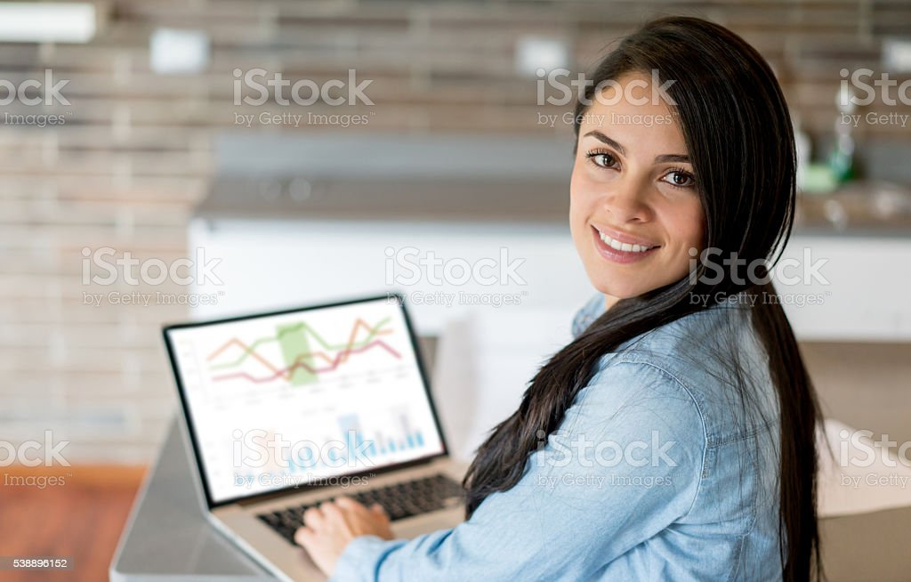 Woman working on a laptop at home stock photo