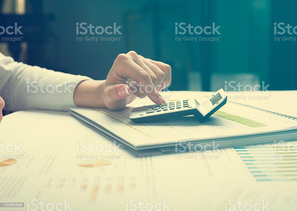 Woman working on calculator analyzing business data stock photo