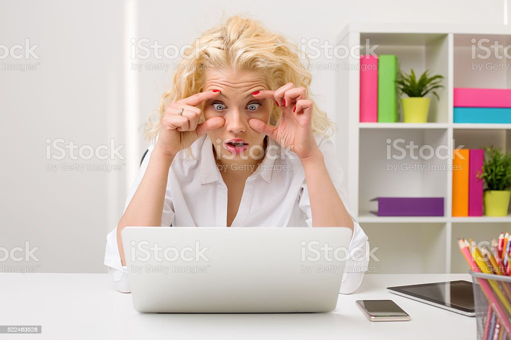 Woman working on computer and holding her eyes open stock photo