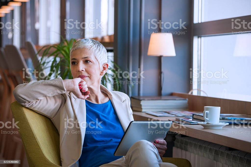 Woman working on digital tablet at cafe stock photo