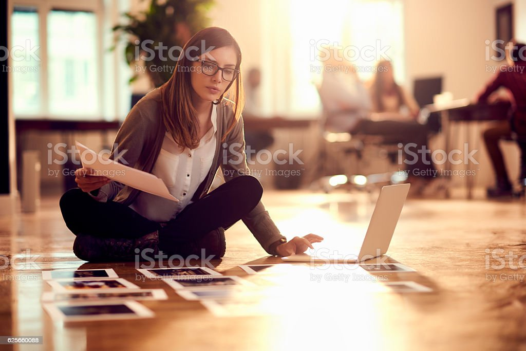 Woman working on floor in office stock photo