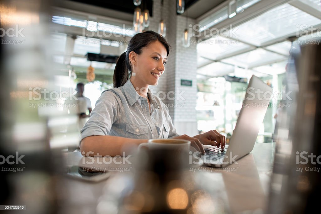 Woman working on her laptop at a cafe stock photo
