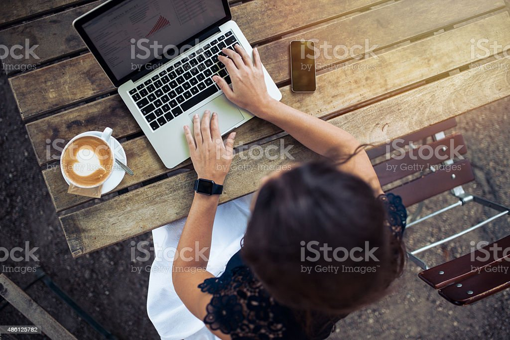 Woman working on her laptop at cafe stock photo