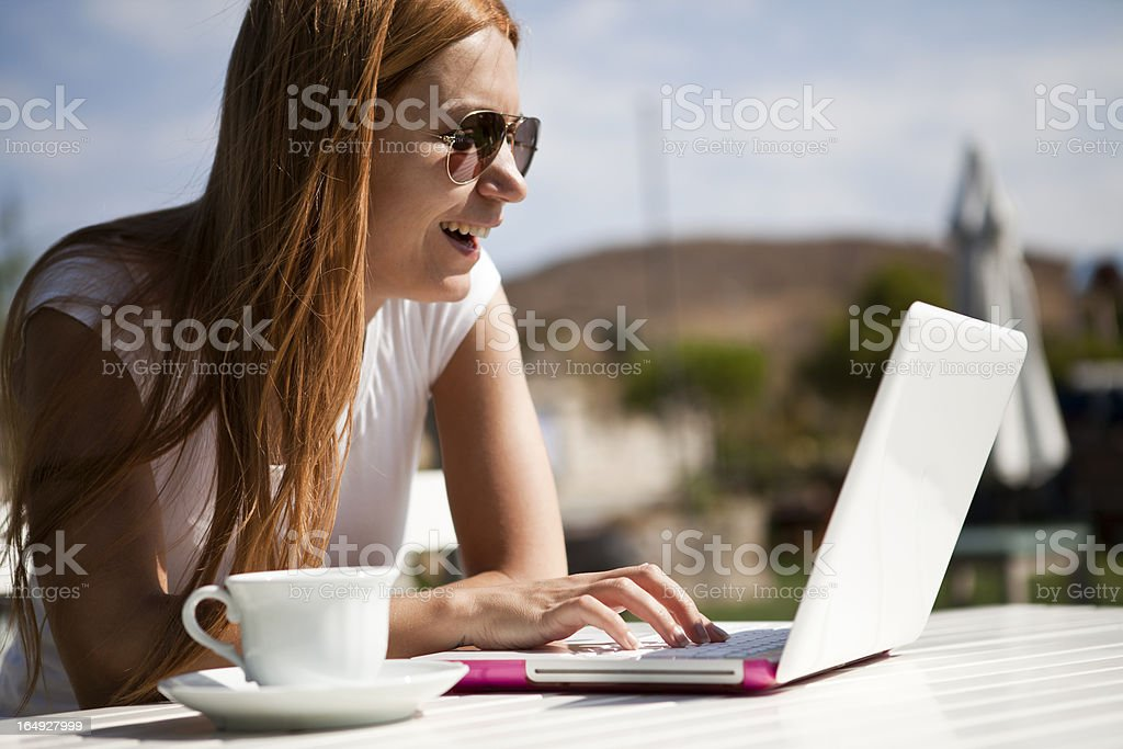 Woman working on her laptop at sidewalk cafe royalty-free stock photo