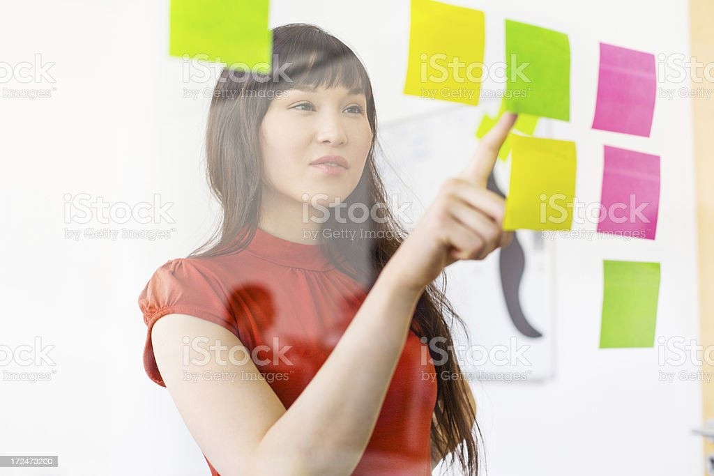 Woman working on her todos looking through glass royalty-free stock photo