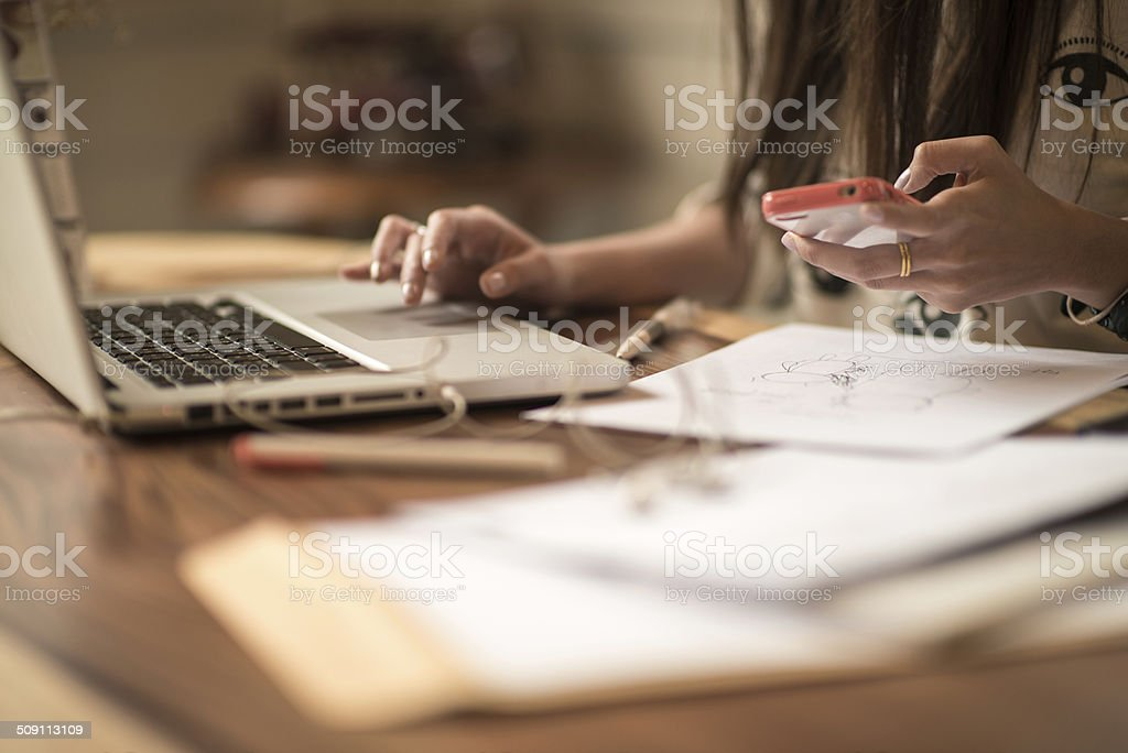 Woman working on laptop and mobile phone stock photo