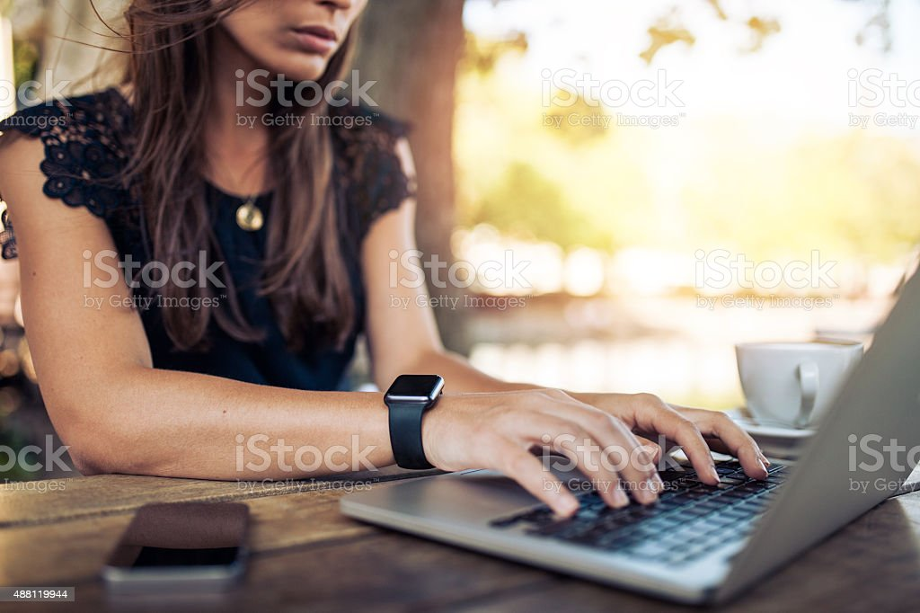 Woman working on laptop in a cafe stock photo
