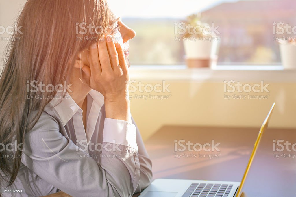 Woman working on laptop in afternoon sun stock photo