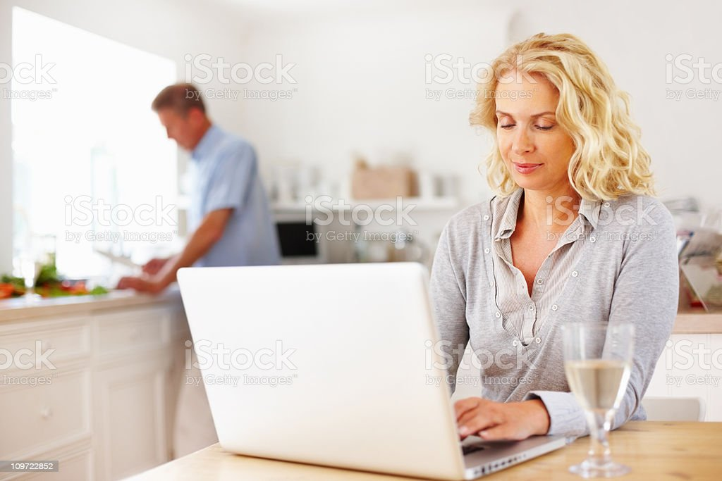 Woman working on laptop while man cutting vegetables in kitchen royalty-free stock photo