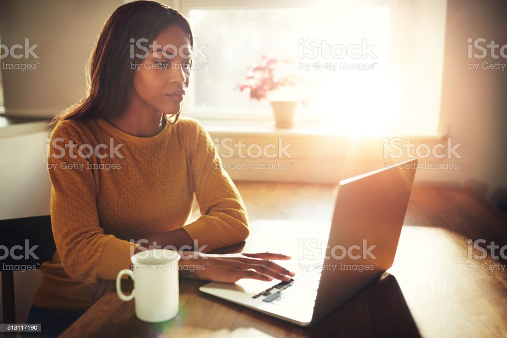 Woman working on laptop with bright sunlight stock photo