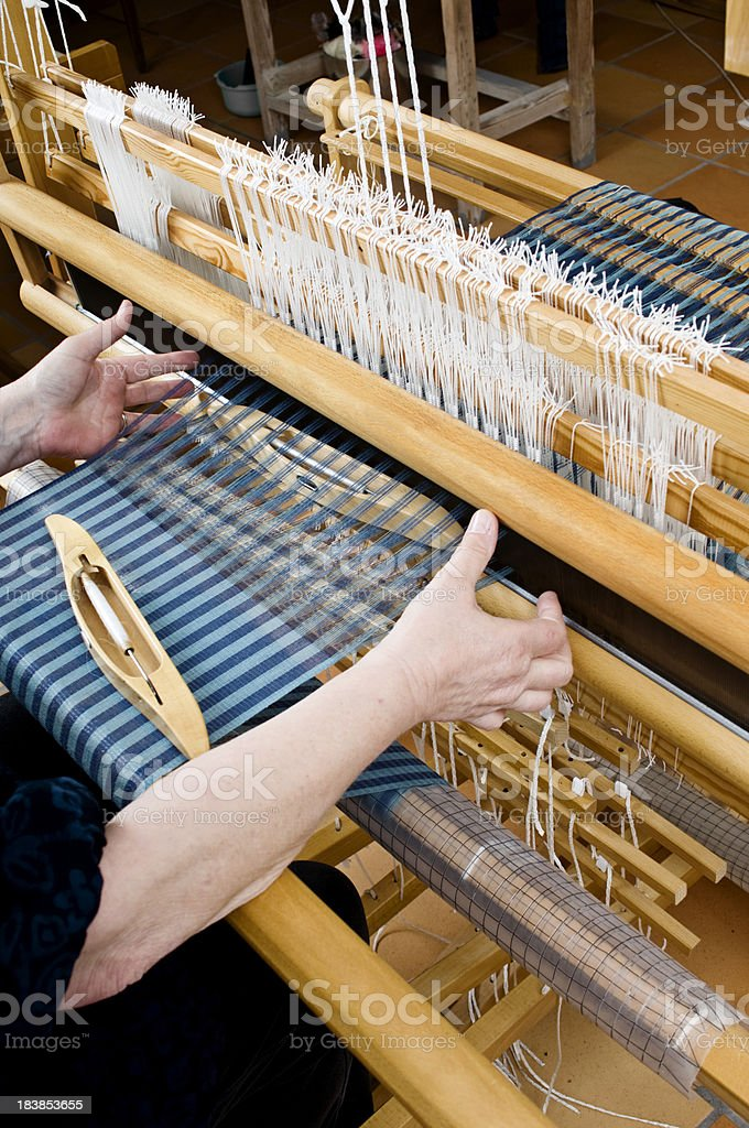 Woman Working On Some Patterned Material Being Woven on  Loom royalty-free stock photo