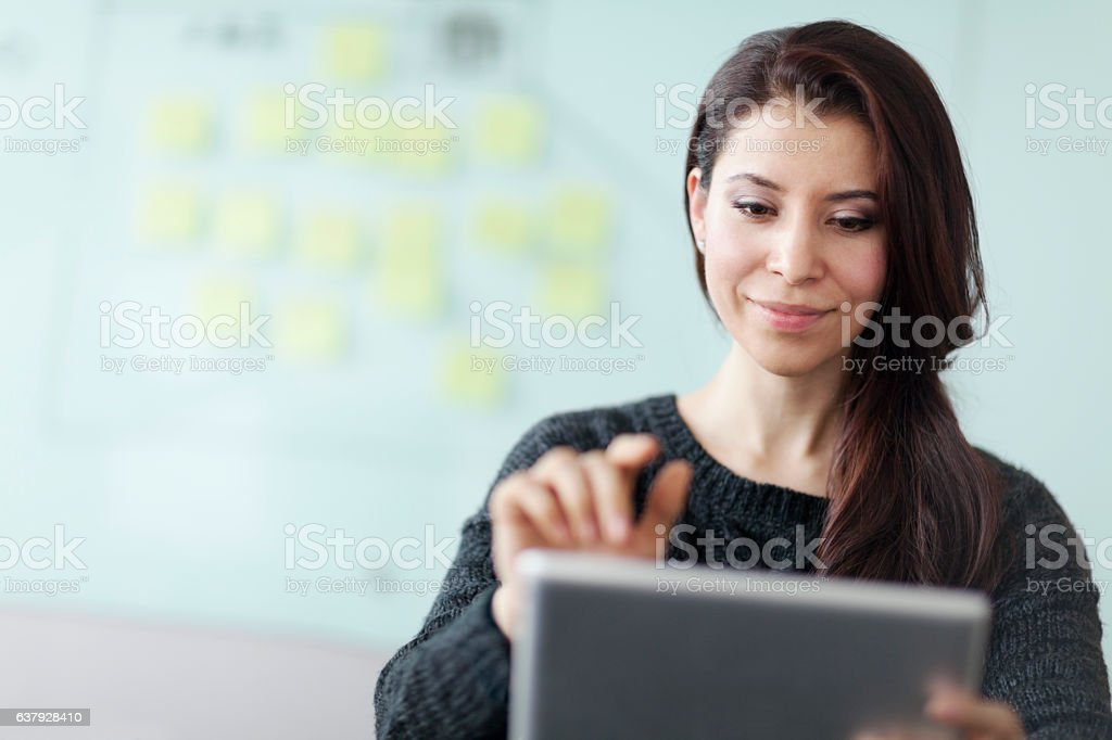 Woman working on tablet computer in studio office stock photo