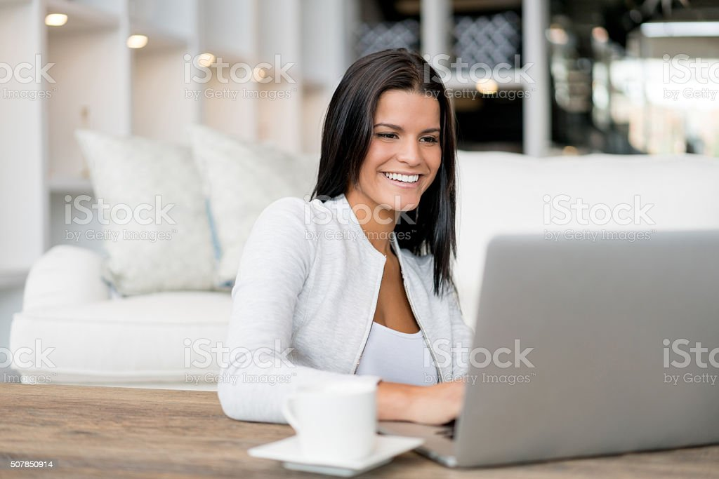 Woman working oon a laptop at home stock photo