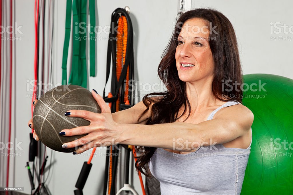 Woman working out in gym holding weight ball stock photo