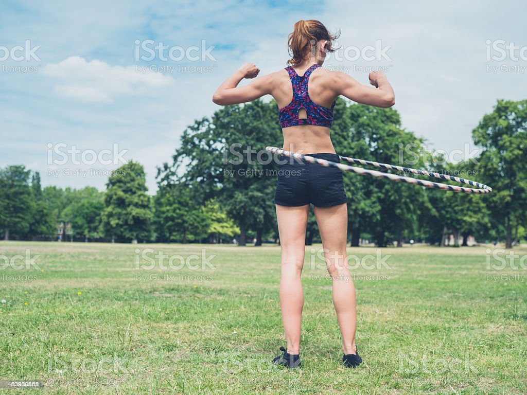 Woman working out with hula hoop stock photo