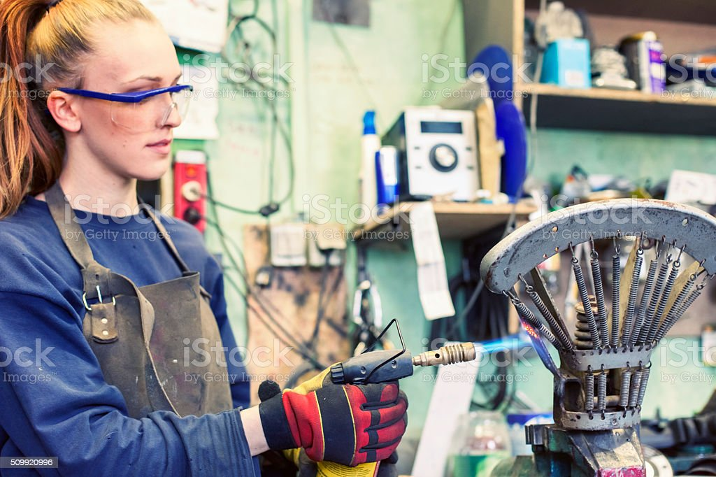 Woman working with a brazing torch stock photo
