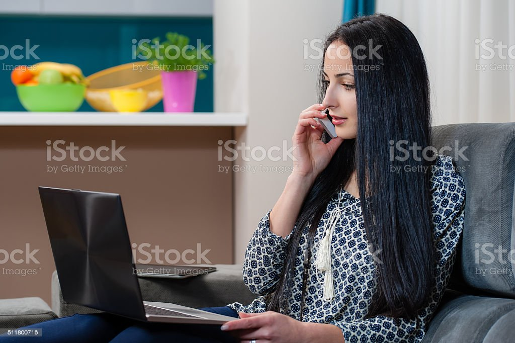 Woman working with a laptop and mobile phone sitting stock photo