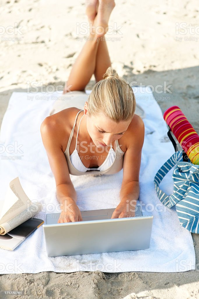 Woman working with a laptop on the beach stock photo