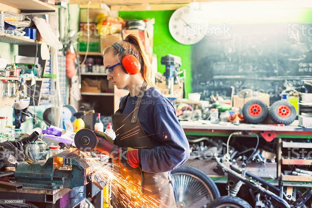 Woman working with an angle grinder stock photo