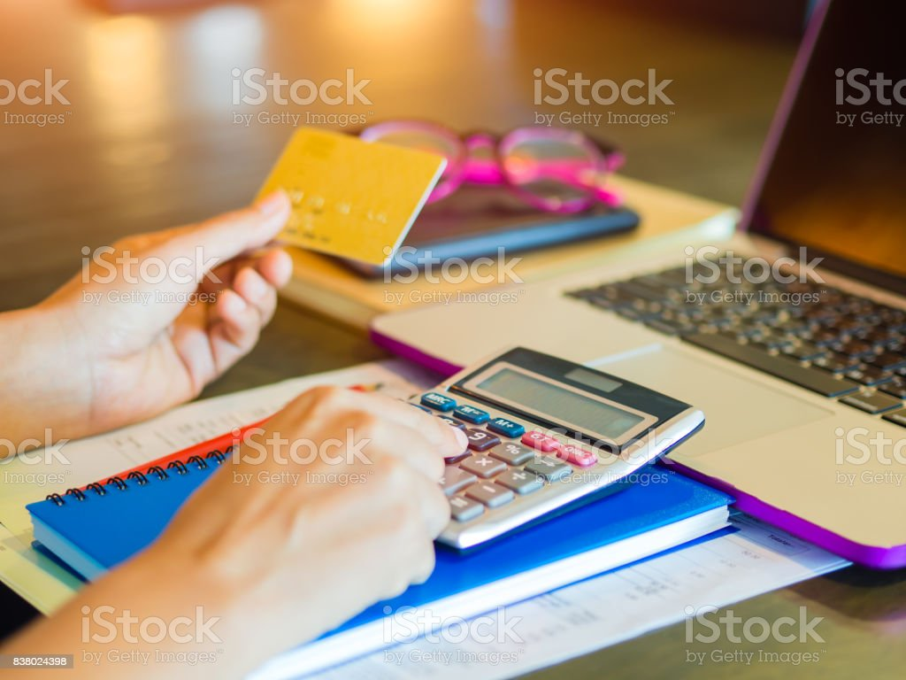 Woman working with calculator, business document and laptop computer notebook stock photo