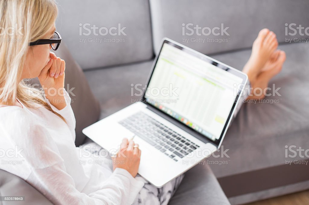 Woman working with computer while sitting on couch stock photo