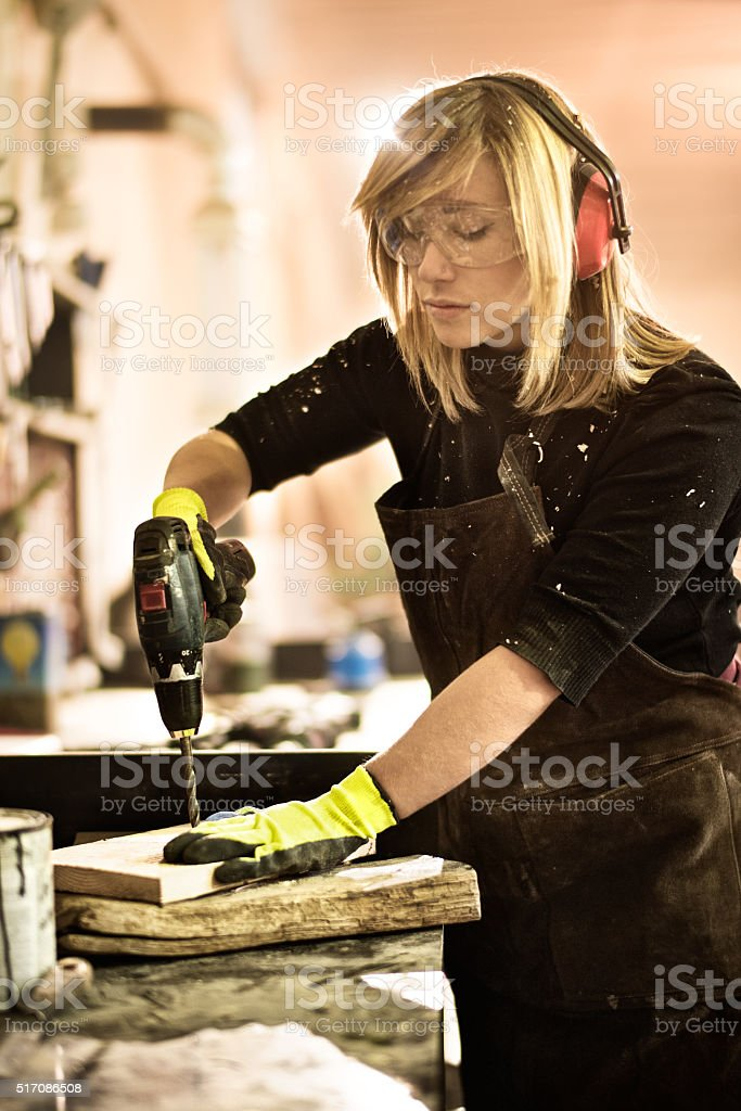 Woman working with electric drill stock photo