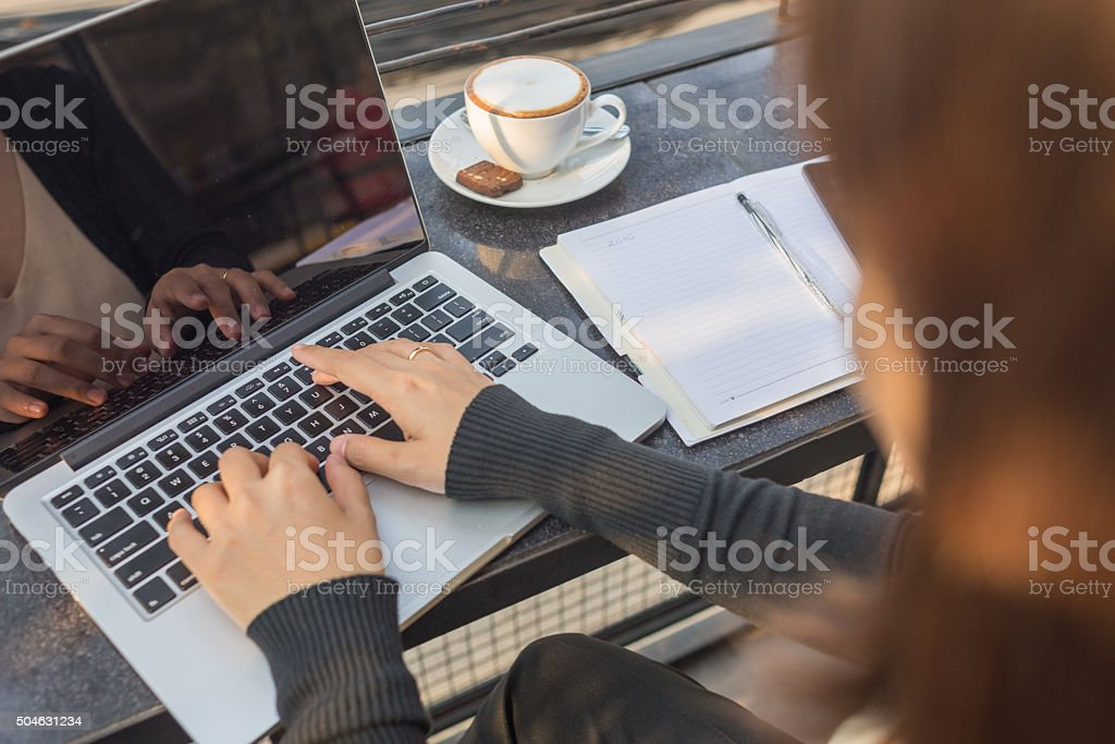 Woman working with laptop and hot cappuccino stock photo