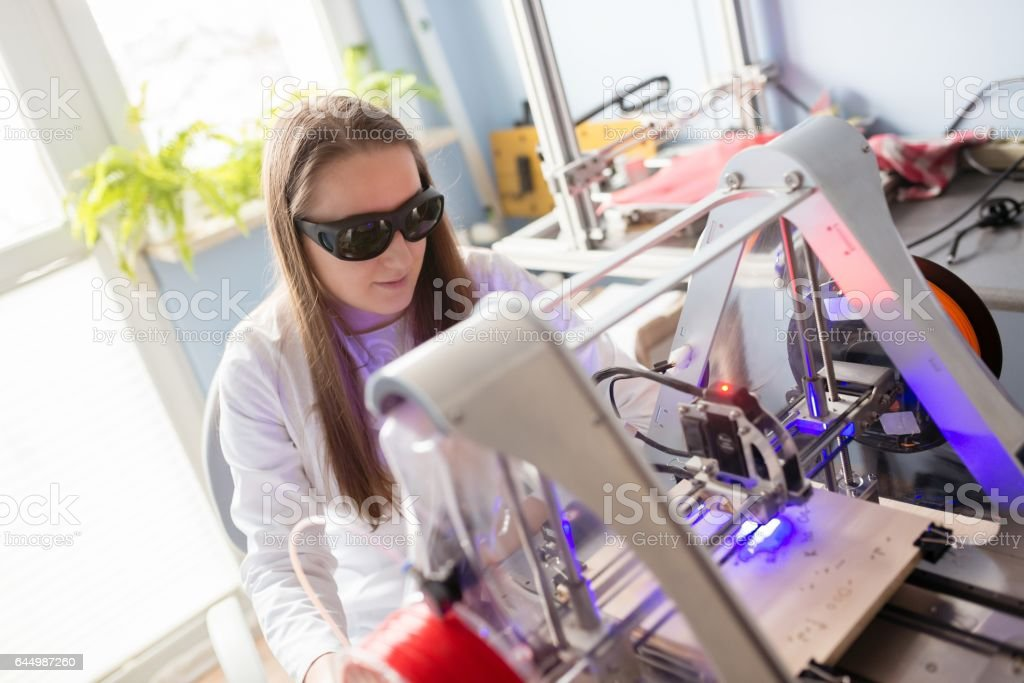 Woman working with laser engraver stock photo