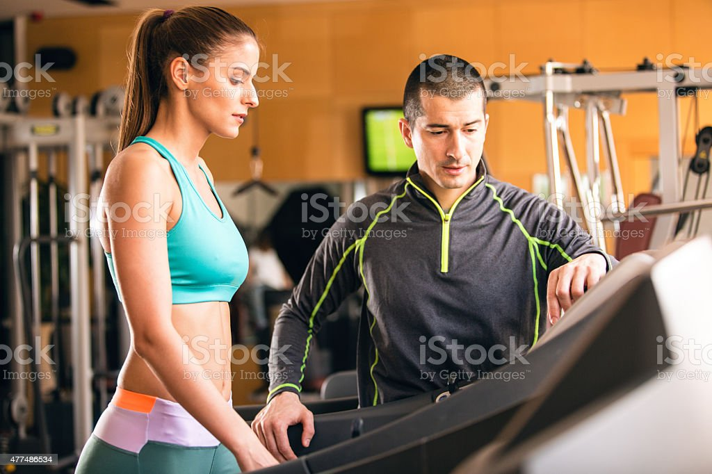 Woman workingout with her personal trainer in gym stock photo
