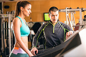 Woman workingout with her personal trainer in gym