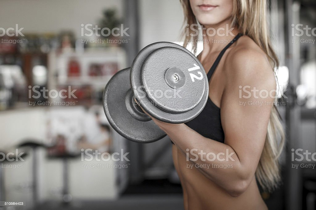 Woman workout with dumbbell in gym royalty-free stock photo